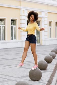 Donkerhuidige gelukkig meisje plezier op een wandeling in de stad in de zomer Premium Foto