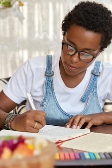 Donkerhuidige hipster in brillen, schrijft in notitieblok, huiswerk