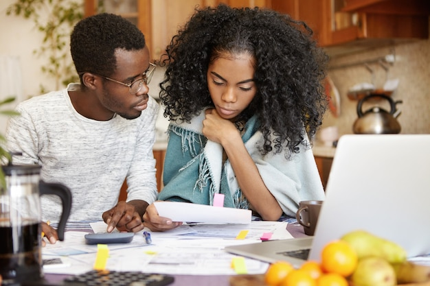 Donkerhuidige man houdt potlood vast, maakt berekeningen op de rekenmachine en kijkt naar zijn bezorgde vrouw