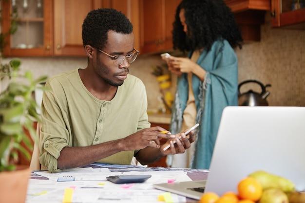 Donkerhuidige man in bril die financiën doet, met behulp van mobiele telefoon, rekenmachine en laptop