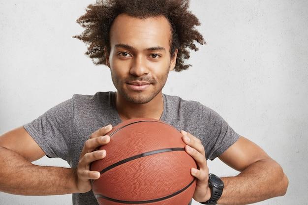 Donkerhuidige man van gemengd ras adverteert basketbal