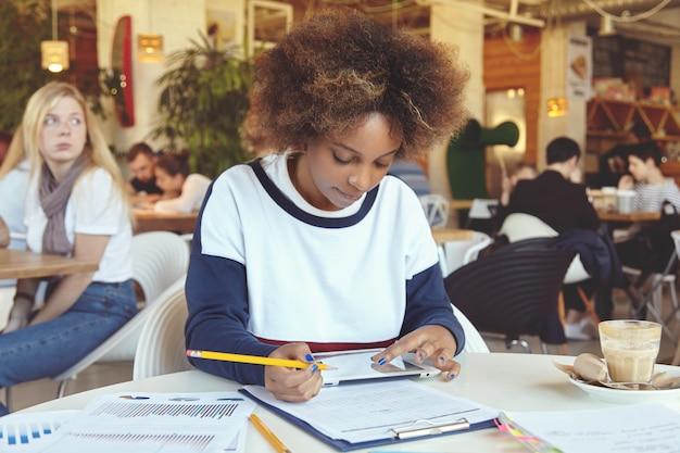 Donkerhuidige student meisje houdt haar vingers op touchscreen tablet, doet thuisopdracht, voorbereiding op les in college kantine, notities maken met potlood, attent en serieus kijken