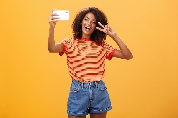 Donkerhuidige vrouw die een selfie neemt die overwinningsteken toont over oranje muur