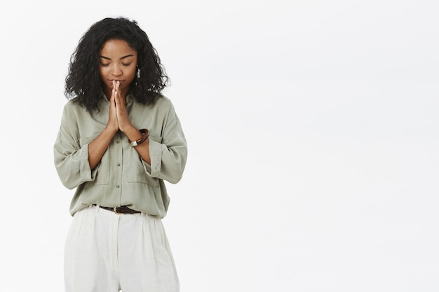 Donkerhuidige vrouw die haar hoofd naar beneden buigt, ogen sluit die vredig en ontspannen staan met de handen in bidden