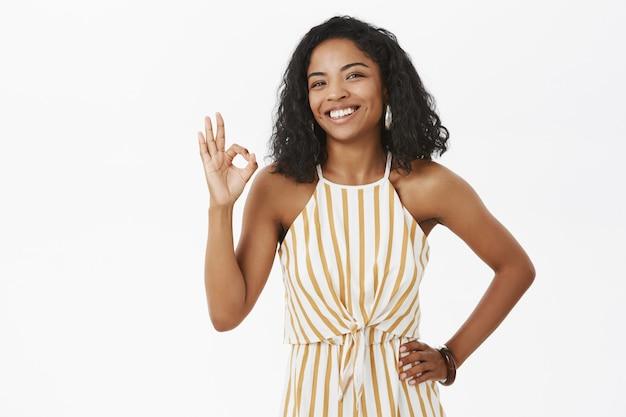Donkerhuidige vrouw met hand op taille met goed gebaar