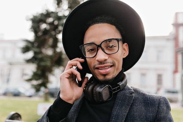 Donkerogige afrikaanse man die zich voordeed tijdens telefoongesprek. buiten close-up foto van emotionele zwarte man zit in park met smartphone.