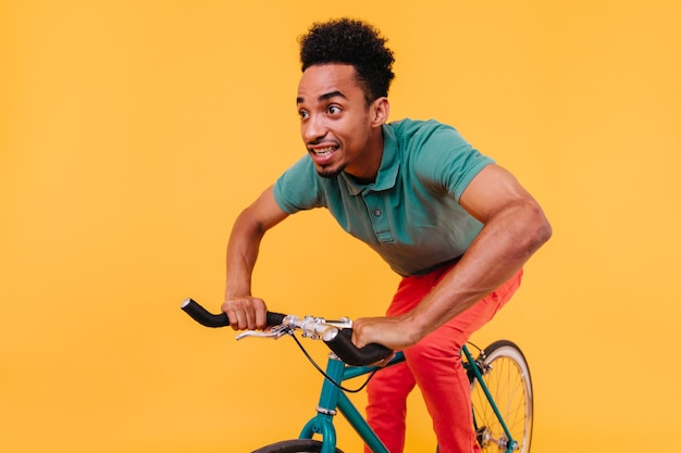 Donkerogige jongeman in groen t-shirt rijden op de fiets. gelukkig afrikaanse man in casual kleding zittend op de fiets.