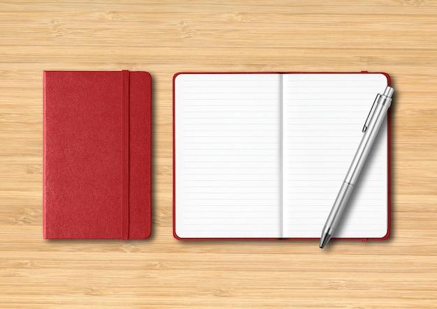 Donkerrode gesloten en open gelinieerde notitieboekjes met een pen