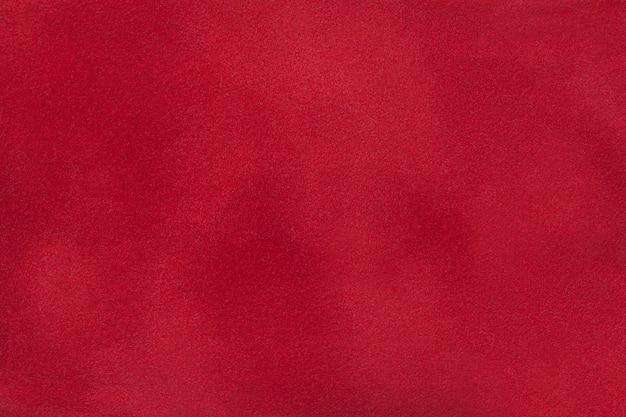 Donkerrode matte achtergrond van suède stof, close-up.