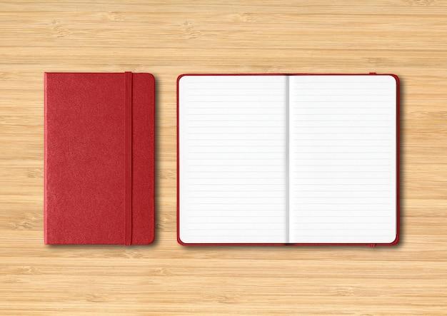 Donkerrood gesloten en open bekleed notitieboekjemodel dat op houten wordt geïsoleerd