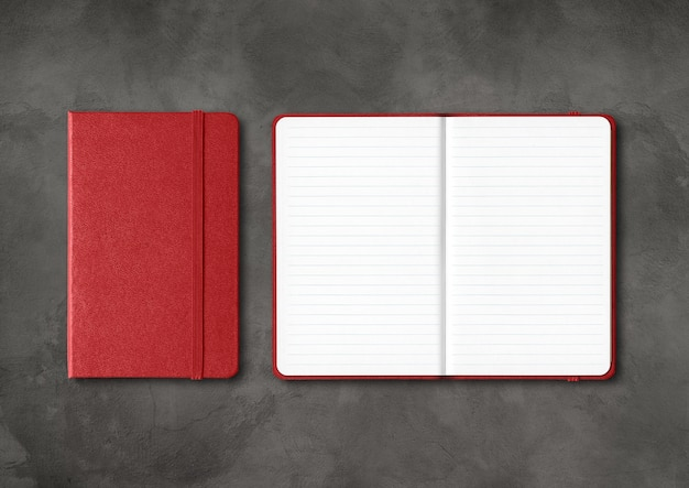 Donkerrood gesloten en open bekleed notitieboekjemodel dat op zwarte concrete achtergrond wordt geïsoleerd