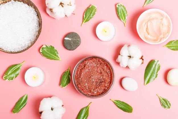 Donkerroze bodyscrub, crème, badzout, kaarsen, katoen en groene bladeren op een roze achtergrond. spa en persoonlijke verzorging. schoonheid plat lag.