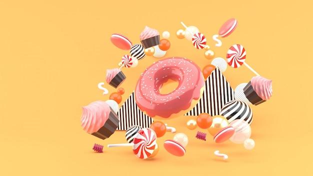 Donut, cupcakes, macaron, candy zwevend tussen kleurrijke ballen onn oranje. 3d render