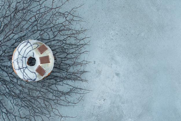 Donut geplaatst op een bos van gedroogde takken op marmeren achtergrond. hoge kwaliteit foto