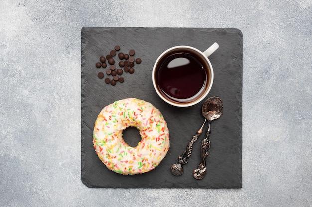 Donut in het glazuur en een kopje koffie op tafel. grijze betonnen tafel, kopieer ruimte.