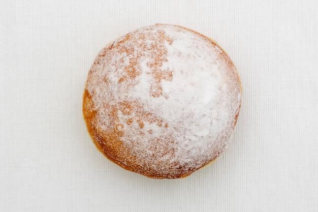 Donut in poedersuikerijs op een lichte ondergrond