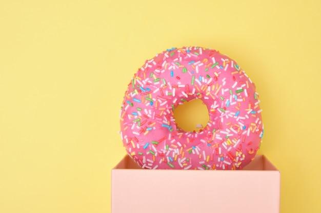 Donut met hagelslag en roze glazuur in een geschenkdoos op een gele ondergrond bovenaanzicht kopie ruimte