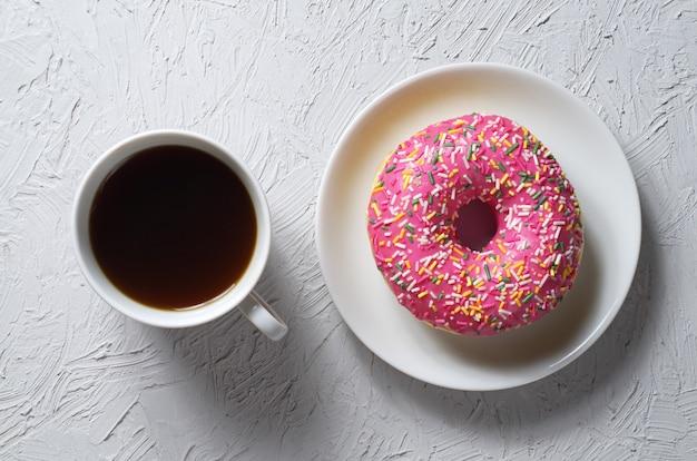 Donut met kleurrijke suikerglazuur en kopje koffie op lichtgrijze stenen achtergrond