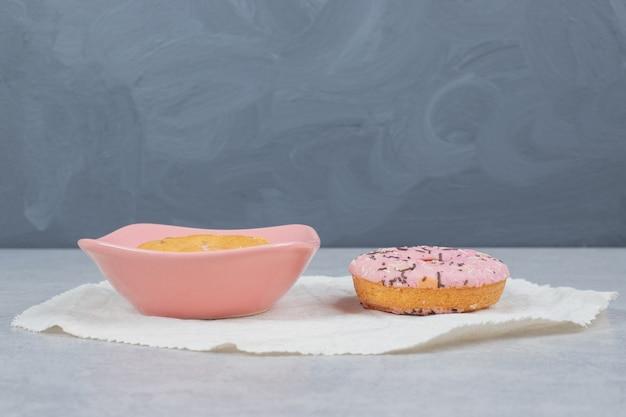 Donut met sproeiers en kom met cake op marmeren tafel.
