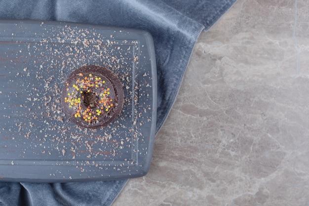 Donut op een kleine chocoladetaart op een bord op marmer