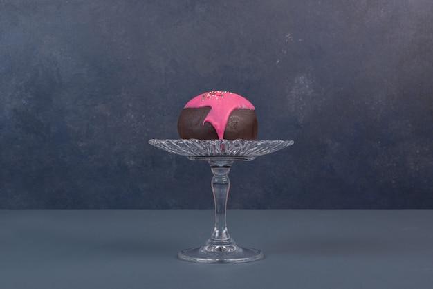 Donut op glasplaat op marmeren achtergrond.