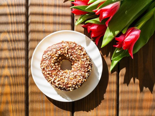 Donut op wit bord met rode tulpen op een bruin houten oppervlak. ontbijt in de zomer, bovenaanzicht