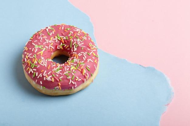 Donutring op gescheurde pastel papier achtergrond.