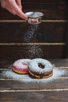 Donuts besprenkeld met poedersuiker op houten tafel op zwart