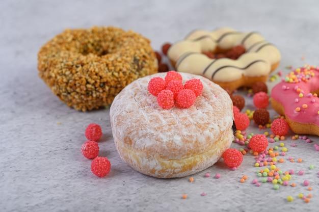 Donuts bestrooid met poedersuiker en snoep op een witte ondergrond.