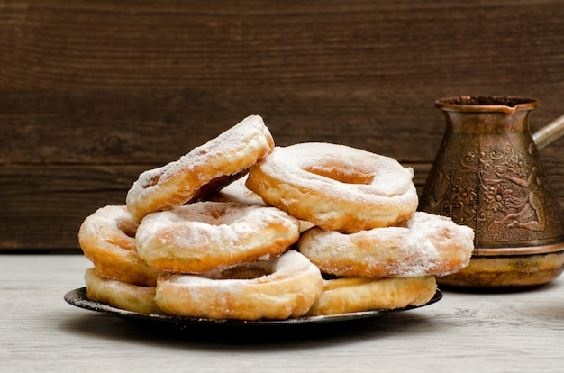 Donuts bestrooid met poedersuiker, koffiepotten, donkere houten achtergrond. close-up, zijaanzicht