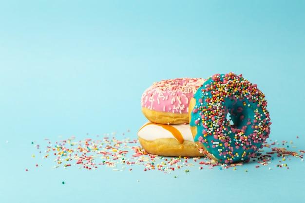 Donuts (donuts) van verschillende kleuren op een blauwe achtergrond met veelkleurige feestelijke suiker hagelslag. vakantie en snoep, bakken voor kinderen, suiker concept