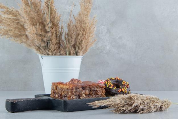 Donuts en een bakhlava op een klein dienblad naast bundels van verengrasstengels op marmeren achtergrond.