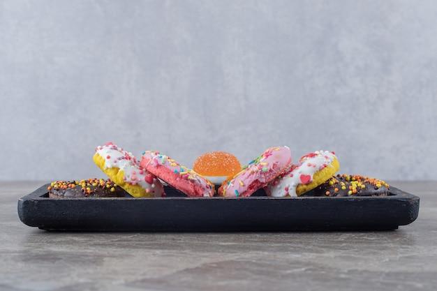 Donuts en een marmelade gebundeld op een zwart dienblad op een marmeren oppervlak