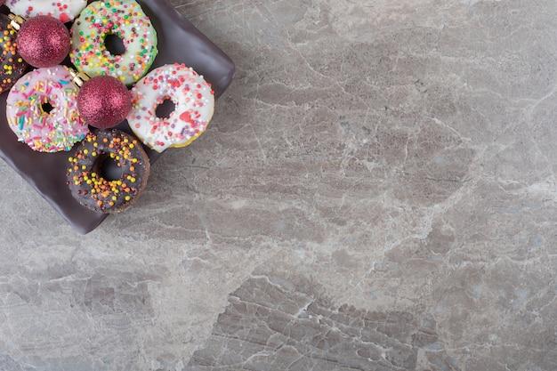 Donuts en kerstballen gerangschikt op een schaal op een marmeren oppervlak