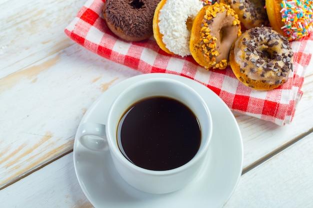 Donuts en koffie op een witte houten achtergrond.