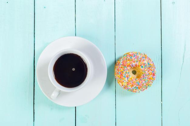 Donuts en koffie op houten tafel. bovenaanzicht