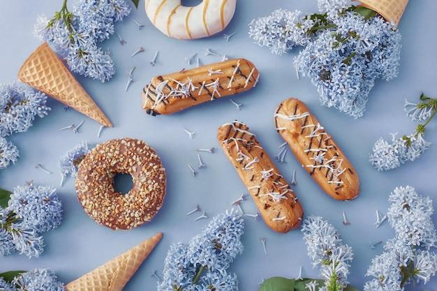Donuts en slagroomtaartjes met lila bloemen op blauw papier