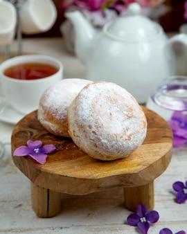 Donuts gegarneerd met bloemsuiker en een kopje zwarte thee