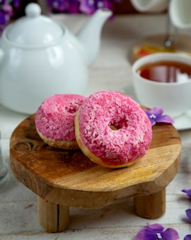 Donuts gegarneerd met meringue en een kopje zwarte thee