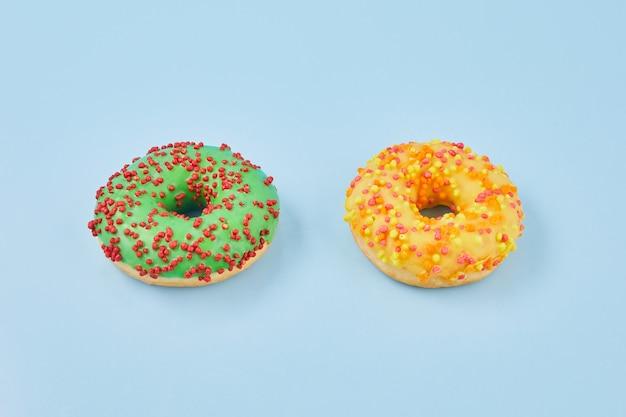 Donuts geglazuurd met hagelslag op pastel blauwe achtergrond. zoete donuts op blauw papier.