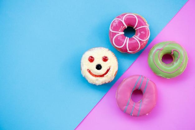 Donuts geglazuurd met hagelslag op roze blauw en pastelkleur