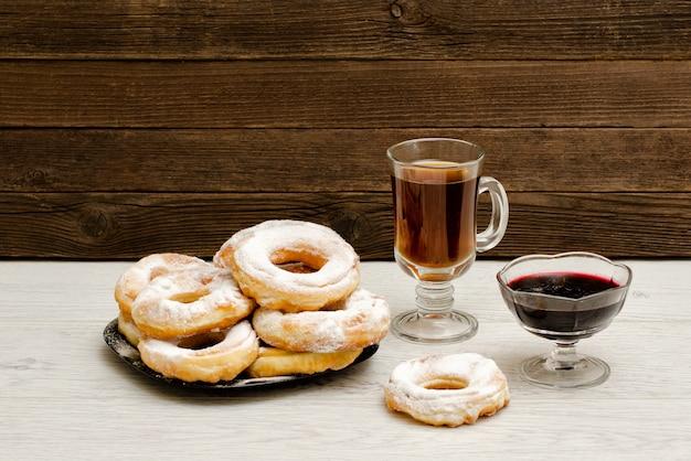 Donuts in poedersuiker, een mok thee en bessenjam op een houten achtergrond