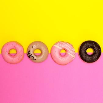 Donuts ingesteld op een gekleurde achtergrond. platliggende fastfoodkunst