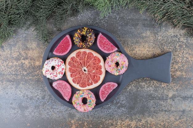 Donuts, marmelades en een grapefruitschijfje netjes gerangschikt in een serveerschaal op een houten oppervlak