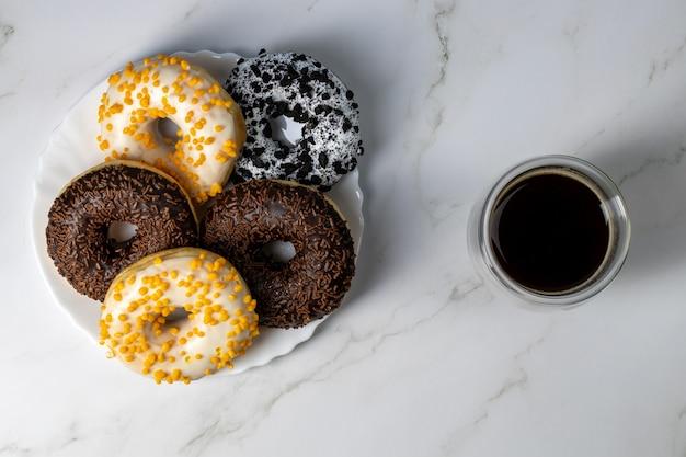 Donuts op een witte plaat op een marmeren tafel en koffie