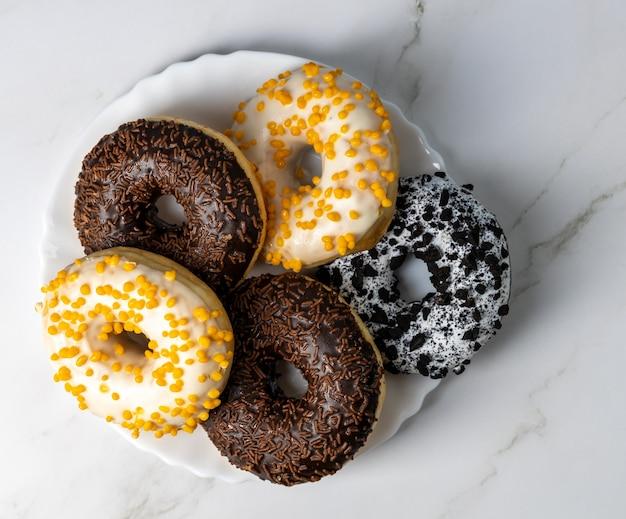 Donuts op een witte plaat op een marmeren tafel