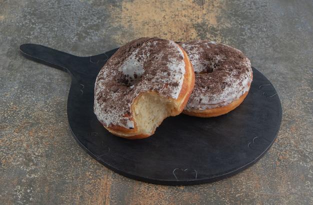 Donuts op een zwarte houten plank