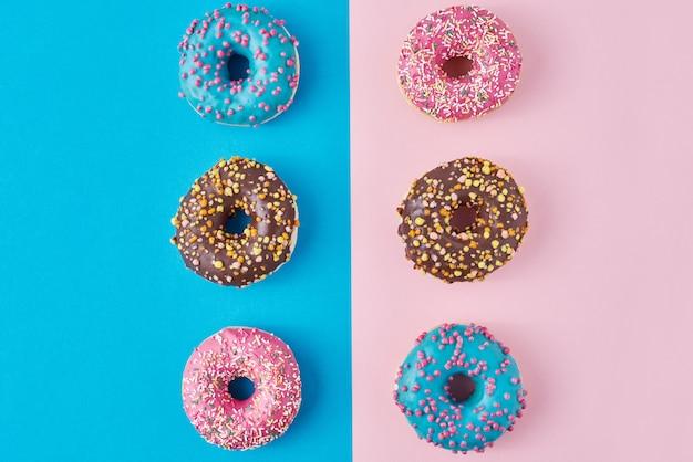 Donuts op pastel roze en blauwe achtergrond. minimalisme creatieve voedselsamenstelling. vlakke stijl