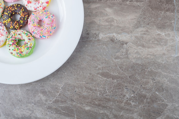 Donuts ter grootte van een snack geserveerd op een witte schaal op een marmeren oppervlak