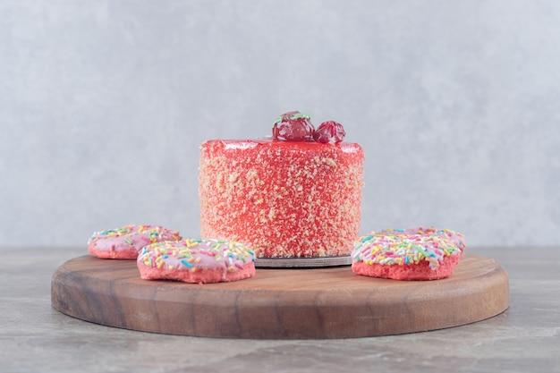 Donuts ter grootte van een snack rond een cake gegarneerd met aardbeiensiroop op een bord op een marmeren oppervlak